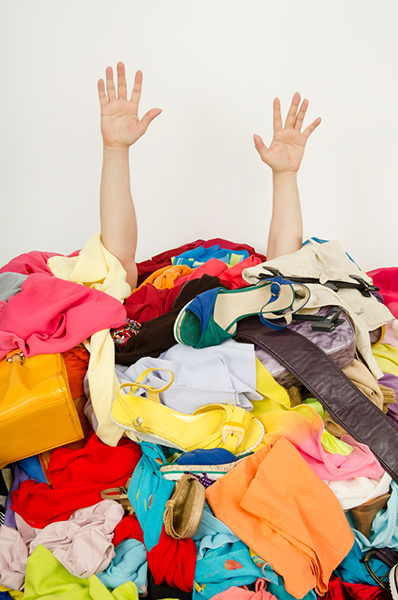 Underperforming keywords clutter PPC campaign strategy, remove them to save money and improve results. Two arms stick out from under a pile of clothes.