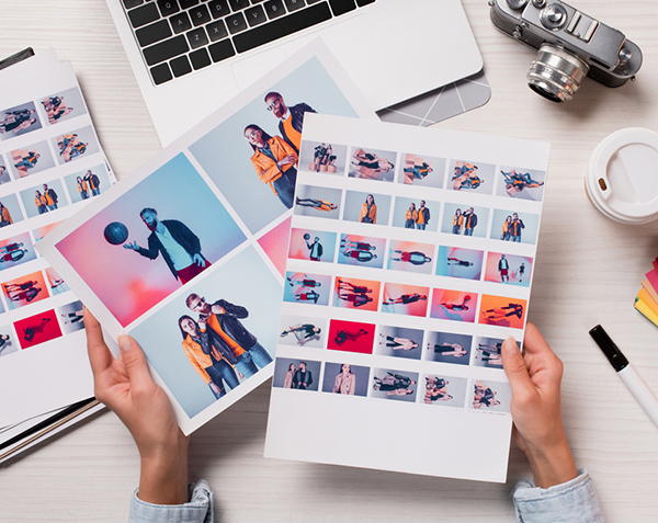High-quality images are a must for mobile design and SEO. Hands hold photo sheets amidst laptop, camera, and coffee at a desk.