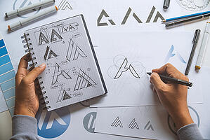 "Researching your logo design will set you up for success. Hands sketch different versions of the letter ""A"" for a logo."