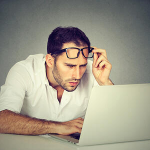 Avoid customer confusion with targeted microsites. A man leans towards his laptop computer, peering and lifting his spectacles.
