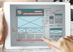The Creative Momentum's team has the skills to make your site look great. Someone touches a tablet devise displaying a wireframe picture.