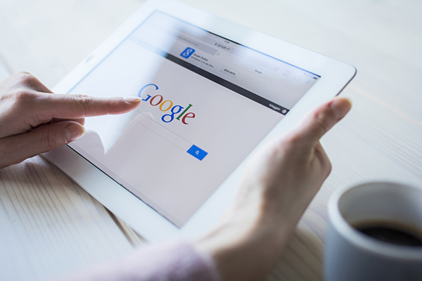 Google's algorithm affects everything about SEO. Hands holding a tablet devise displaying Google's homepage and pointing to the Google logo on the screen.