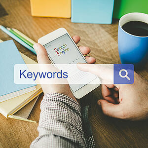 """Keywords are vital in SEO strategy. """"Keywords"""" in a translucent search bar; hands hold a phone at a desk with coffee cup."""