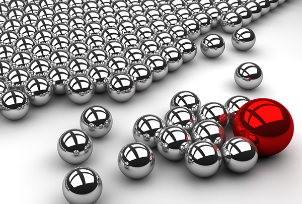 Influencers can affect how your target market thinks about you. Close-up, perspective view from the right side of silver magnetic balls. One larger red ball attracts the silver balls away from the group.