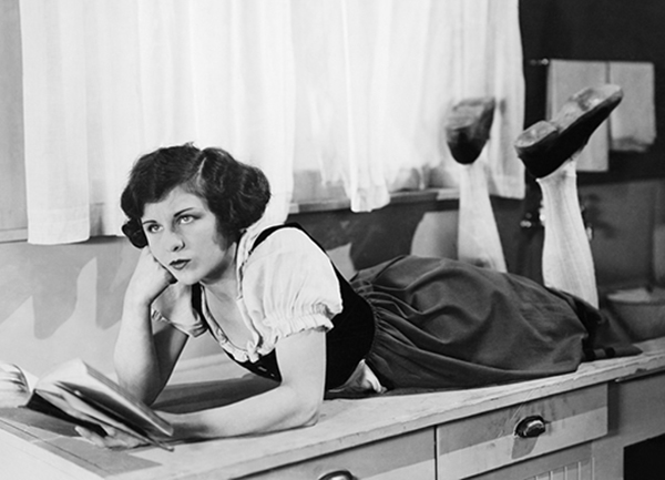 Bored? You probably found a site with no interesting visuals. [vintage photo] Lady, cheek on fist, reads a book on her belly.