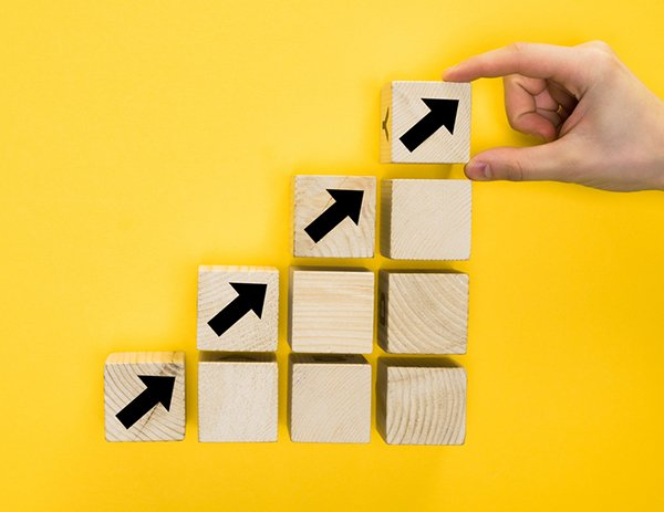 SEO domain authority - how can you improve your domain authority? Wooden blocks in the shape of a staircase with arrows leading up